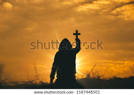 Man raise the cross to sky for praying to God at sunset background. christian silhouette concept.