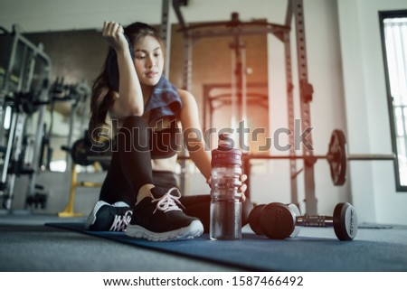 Young woman drinking water and taking a break after workout in gym,fitness concept.blury #1587466492