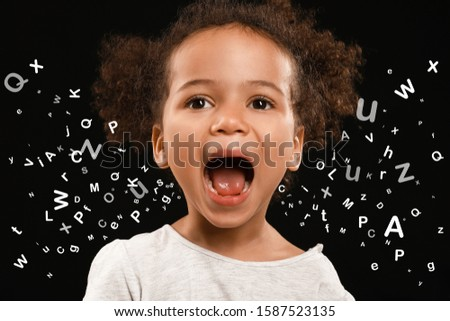 Screaming African-American girl and many letters on dark background Royalty-Free Stock Photo #1587523135