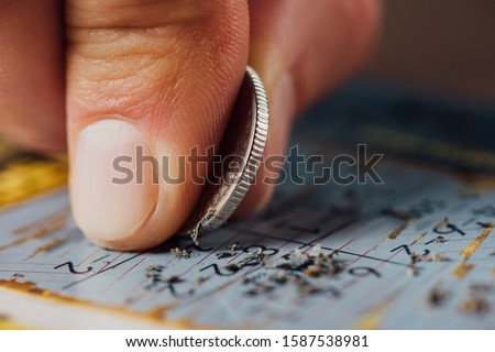 close up view of silver coin in hand of gambler scratching lottery card Royalty-Free Stock Photo #1587538981