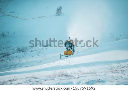 Snow cannon in winter mountains. Snow-gun spraying artificial ice crystals. Machine making snow. Strbske pleso (Strbske lake) ski resort with snow.  #1587591592