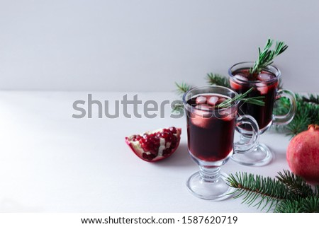 Two glass of pomegranate Christmas cocktail with champagne, soda and rosemary on a white table. Xmas drink. Close up. Copy space. Horizontal orientation. Horizontal orientation. #1587620719