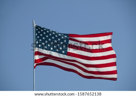 Detail view of the flag of the United States against blue sky #1587652138