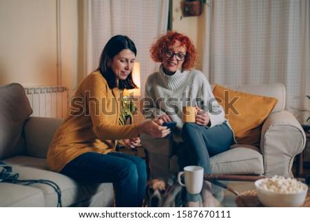 woman friends sitting sofa at home talking #1587670111