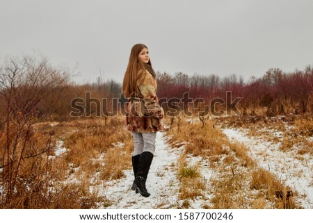 Sad girl in the brown coat waiting for a date in autumn in a park #1587700246