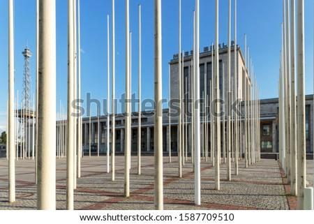 07/24/2015 Berlin, Germany. View of an empty Messe Berlin building (Berlin Messegelände) through dozens of flagpoles, exhibition grounds in the Charlottenburg-Wilmersdorf precinct of Berlin, Germany #1587709510
