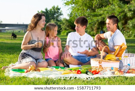 Parents with two teenagers enjoying  delicious meal on the picnic #1587711793