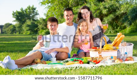 Parents with two teenagers enjoying  delicious meal on the picnic #1587711796