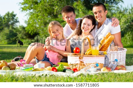 Parents with two teenagers enjoying  delicious meal on the picnic #1587711805
