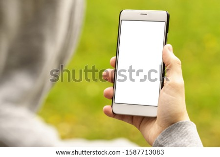 A man in a grey hoodie looking at the phone screen in his right hand. Mockup image of mobile smartphone with blank white screen. #1587713083