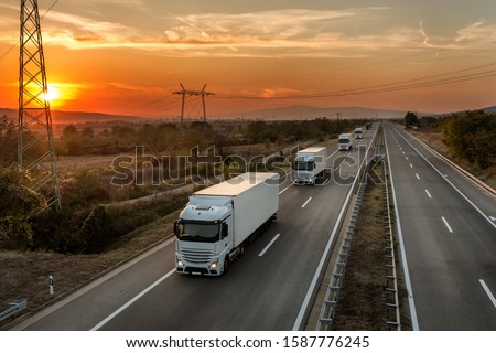 Fleet of blue lorry trucks on a country highway under an amazing orange sunset sky #1587776245