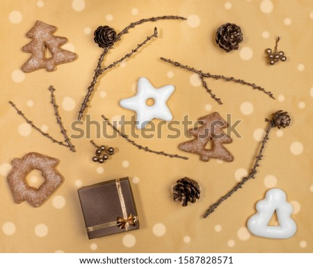 Christmas flat lay layout on golden background. Glazed gingerbread, bronze painted twigs with cones and gift box. #1587828571