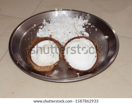 Two halves of a coconut placed with grated portion behind  #1587862933