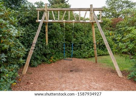 Empty swing on children playground. Children swing in the park,wooden swing, wooden swing on the lawn. #1587934927