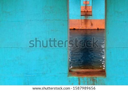 Urban architecture, under the bridge. Turquoise bridge piers extending into the distance #1587989656