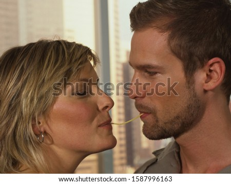 Close up of couple sharing spaghetti noodle #1587996163