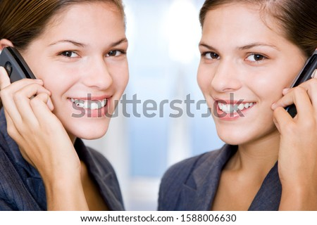 Two identical twin businesswomen using cellphones #1588006630