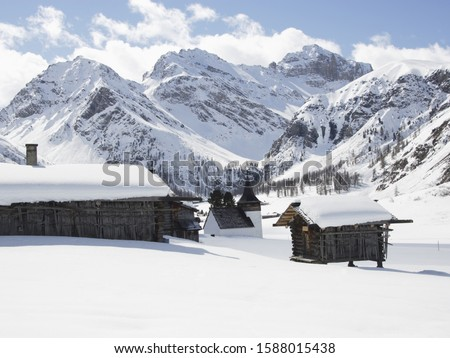 Snow covered huts with mountains in background, Davos, Grisons, Switzerland #1588015438