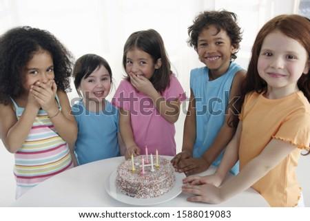 Group of children smiling around birthday cake indoors