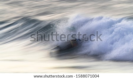 Surfboard  pushed by the waves towards the shore. Low speed shot #1588071004