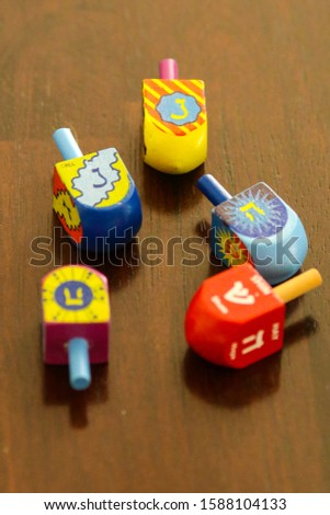 A collection of several colorful, wooden dreidels sitting non a table #1588104133