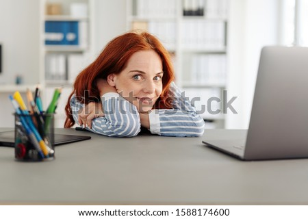Young businesswoman glancing sideways at the camera as she relaxes resting her arms and head on the desk viewed low angle Royalty-Free Stock Photo #1588174600