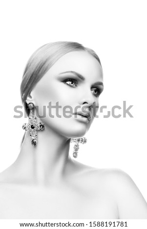 Beautiful fashion model woman studio beauty portrait, perfect skin, bright makeup, blonde hairstyle, earrings color stones, naked shoulder body. Isolated. White background. Copy space. Black and white #1588191781