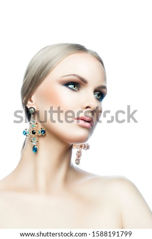 Beautiful fashion model woman studio beauty portrait, perfect skin, bright eye make-up, blonde hair style, big earrings with color stones, naked shoulder body. Isolated. White background. Copy space #1588191799