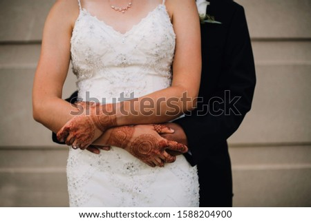 Groom and bridal hugging and bridal showing mehndi hands #1588204900