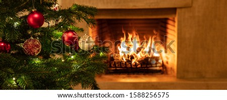 Christmas holiday home background. Warm cozy burning fireplace and Xmas tree decorated, season greetings card template, banner