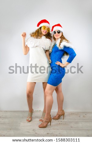 Happy laughing women in Santa hats having fun on a bright backdrop Happy New Year 2020 celebration holiday concept. Mock up copy space.