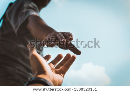 Help Concept hands reaching out to help each other in dark tone. Royalty-Free Stock Photo #1588320151