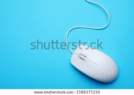 Wired computer mouse on light blue background, top view. Space for text #1588375150