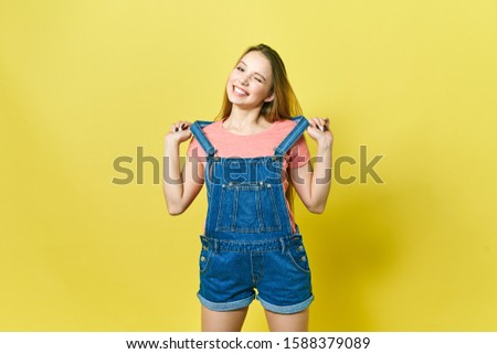 Portrait a pretty girl in denim overalls on a yellow background. Fashionista lady student smiling . Bright trendy studio fashion image of sexy model, wearing neon bright color block clothes, casual #1588379089
