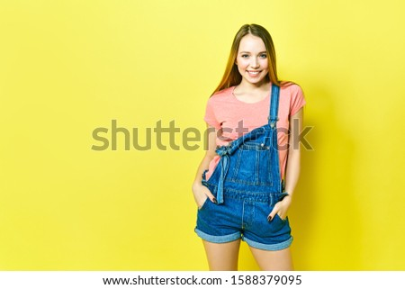 Portrait a pretty girl in denim overalls on a yellow background. Fashionista lady student smiling . Bright trendy studio fashion image of sexy model, wearing neon bright color block clothes, casual #1588379095