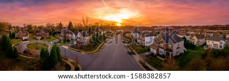 Aerial sunset panorama view of luxury upscale residential neighborhood gated community street in Maryland USA, American real estate with single family homes brick facade colorful sky cul-de-sac #1588382857