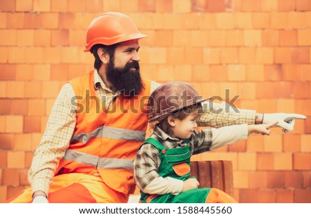 Employee. Beautiful photo about the construction site. Brick wall and two workers. Little son and adult father. Professional education. Future builder. #1588445560