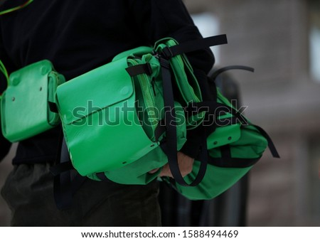 Man carries a green textile bag with black straps in his hand #1588494469