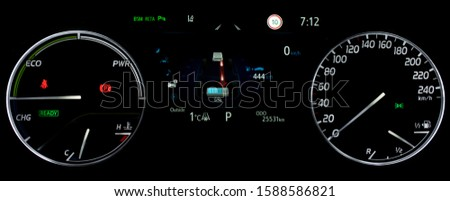 Car dashboard in hybrid car. Close up shot of display indicating battery charge level, speedometer, power monitor, odometer, fuel gauge. Car counter showing energy monitor of engine and battery use.