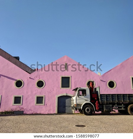 truck on the background of a house with pink walls. industrial machinery or motor transport. lots of pink houses on a blue background.  #1588598077