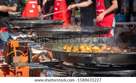 Cullera, Valencia / Spain - October 5, 2019: People are cooking a traditional Paella in Valencia on the street on a big pan during a paella competition in Cullera, Spain. Spanish Mediterranean diet. #1588631227