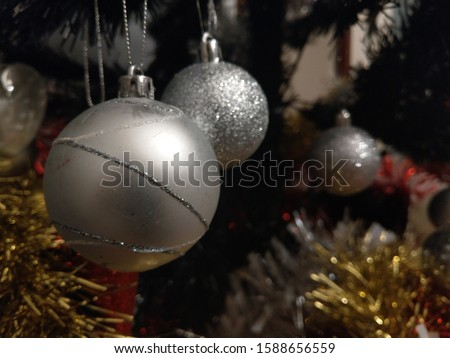 silver bauble infront of other baubles hanging on a tree with gold and red tinsel in view #1588656559