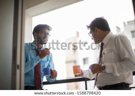 Corporate meetings with coffee/tea  and cigarette between young and energetic Indian Bengali bosses/officers/managers at balcony of the office building regarding a project. Indian corporate lifestyle #1588798420