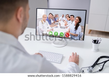 Young Male Doctor Video Chatting On Laptop In Clinic #1588829416