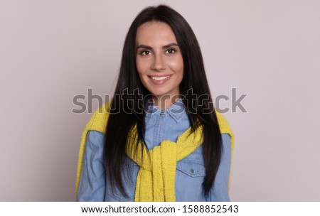 Close-up photo of a nice woman in denim outfit, who is posing in front of the camera, looking in the camera and smiling sincerely. #1588852543