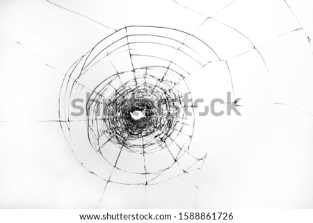 Cracks on broken glass. The window is damaged by a shot from a firearm. Transparent windscreen of a car with a hole after the shots. Royalty-Free Stock Photo #1588861726