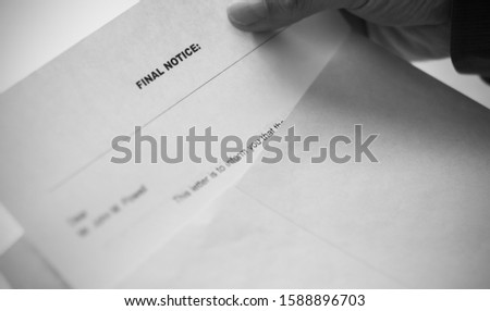 Taking a letter from the envelope with the notice: FINAL NOTICE. Photo in black white. #1588896703