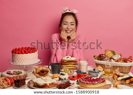 Feminine girl smiles pleasantly, keeps both hands under chin, dressed in knitted rosy sweater, poses at table with sugary desserts and bakery, thinks what to eat first, isolated over pink background #1588900918