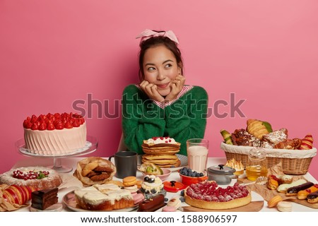 Unhealthy nutrition and much calories concept. Thoughtful brunette Asian woman poses at festive table, looks aside, has doubts eat or not, surrounded with many bakery products, wears green jumper #1588906597