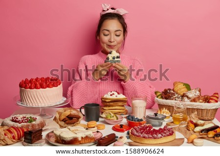 Photo of adorable Korean woman holds yummy sugary dessert or muffin, isolated over pink background, tastes fresh baked confectionery, cant imagine life without sweet dishes, dressed casually #1588906624